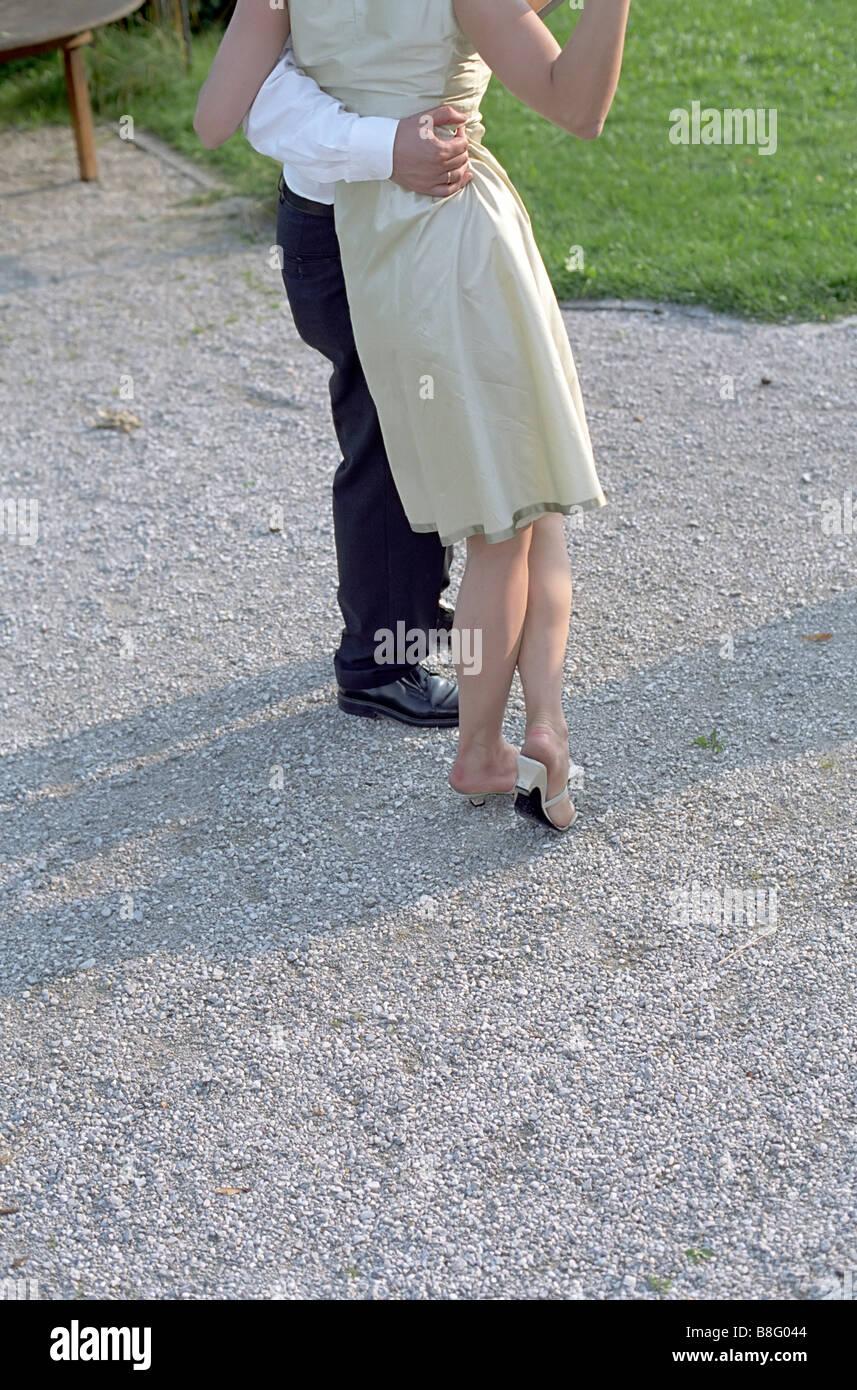 Man hugging a Woman in a Dress - Family Celebration - Garden - Togetherness - Flirt - Stock Image