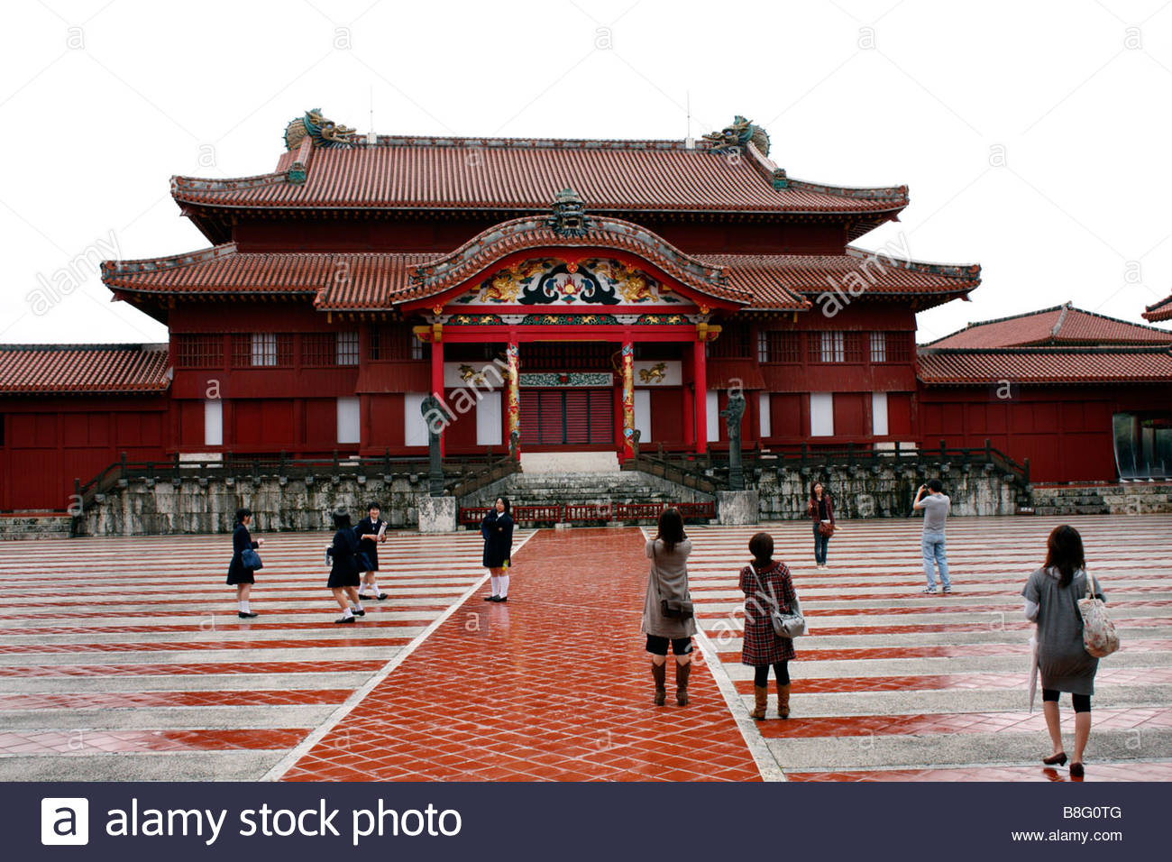 Tourists in the courtyard in front of the Palace of the Ryukyu Kings, Shurijo Castle Park, Okinawa Japan - Stock Image