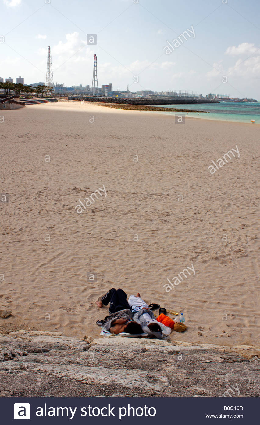 Young couple sleeping on Tropical Beach, almost deserted in mid morning; Naha, Okinawa, Japan - Stock Image