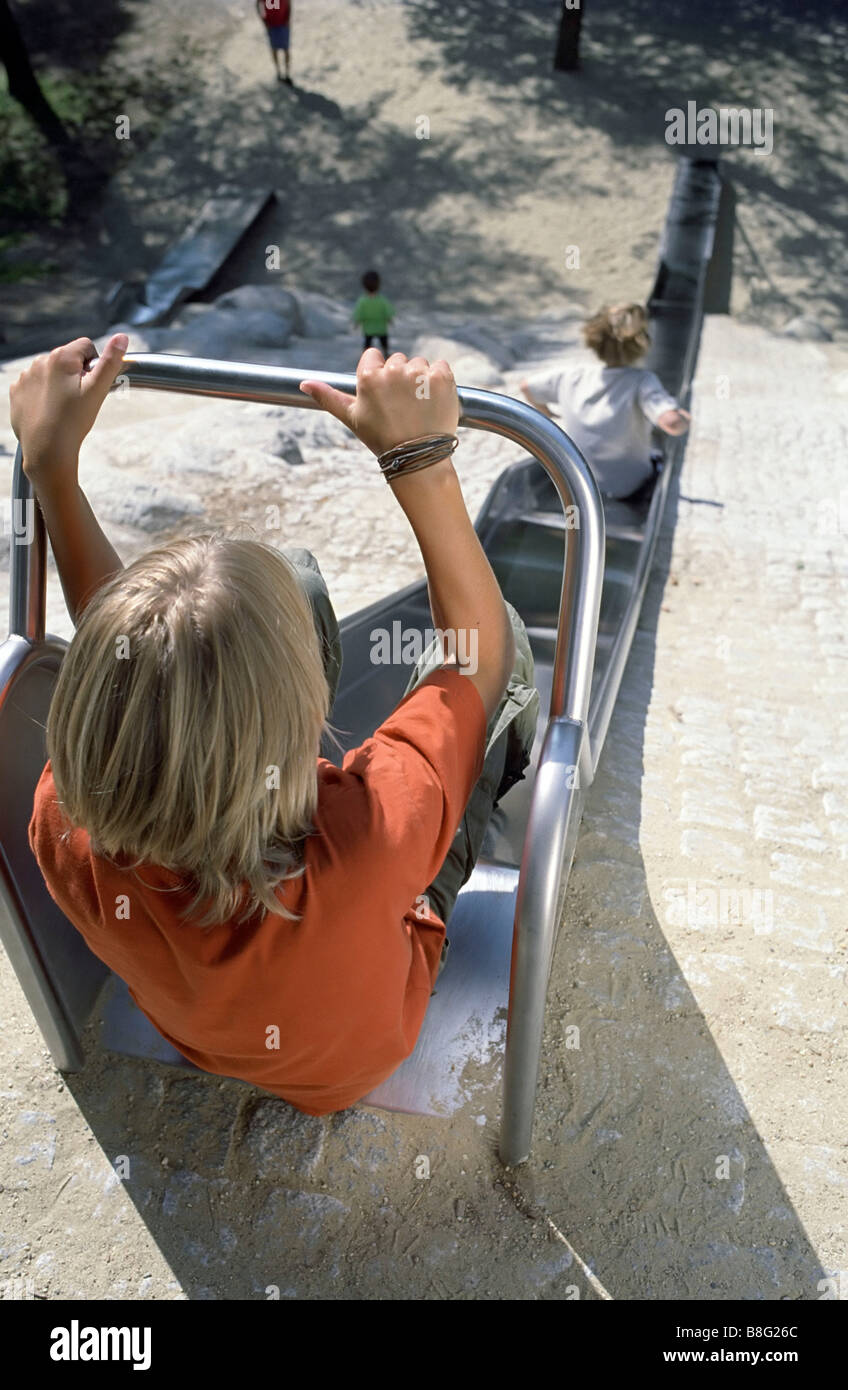 Blonde Boy at the upper End of a Slide - Playground - Summer - Stock Image