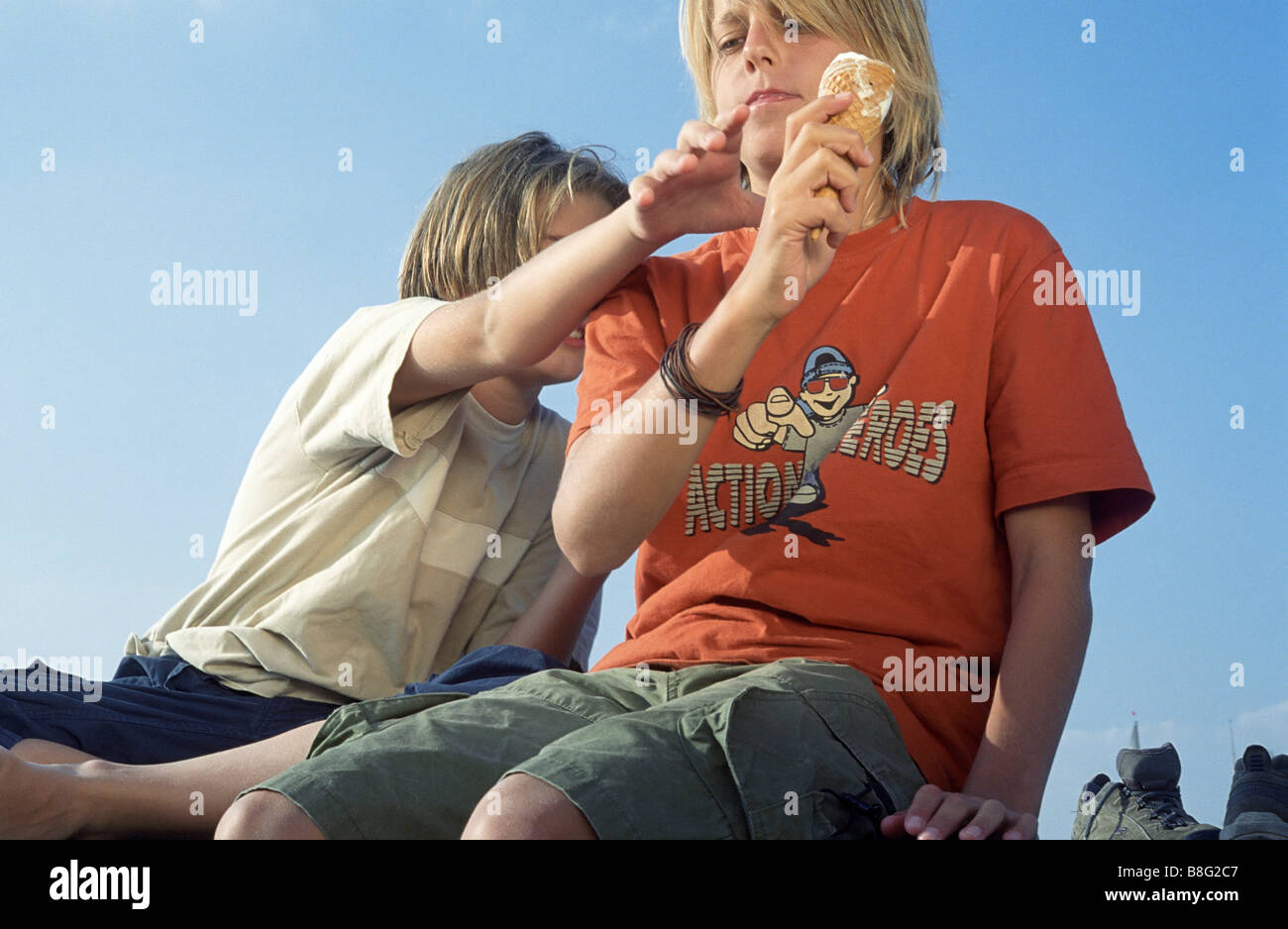 Boy grasping at the Ice-cream of his Friend - Scene - Sweets - Disagreement - Stock Image