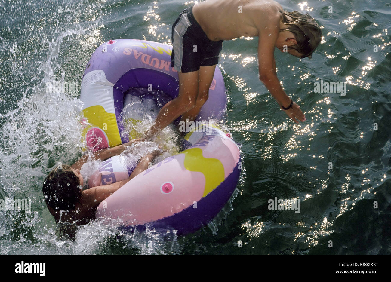 Two Boys jumping out of a Rubber Dinghy at the same Time - Fun - Youth - Lake Stock Photo