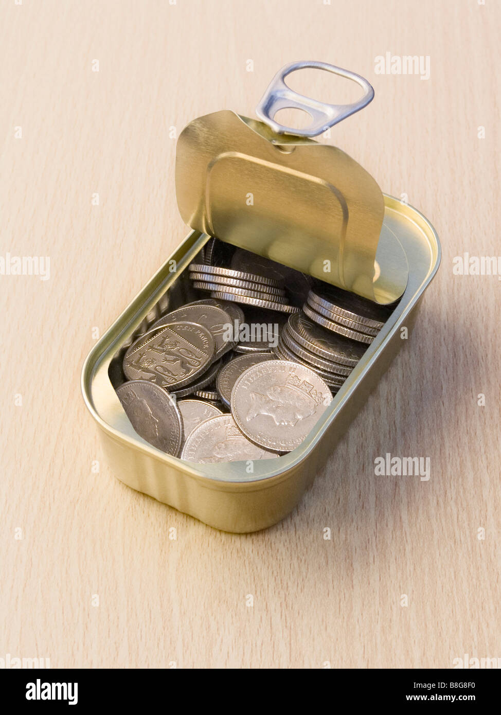 Ring Pull Tin Can Containing Ten Pence Pieces on a Wooden Surface - Stock Image