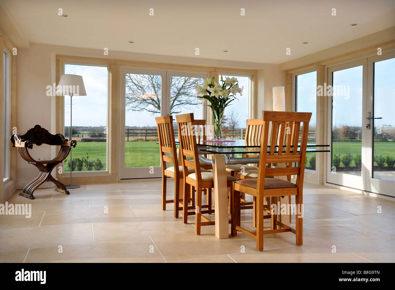 A DINING ROOM SURROUNDED BY PATIO DOORS IN MODERN COUNTRY HOME UK