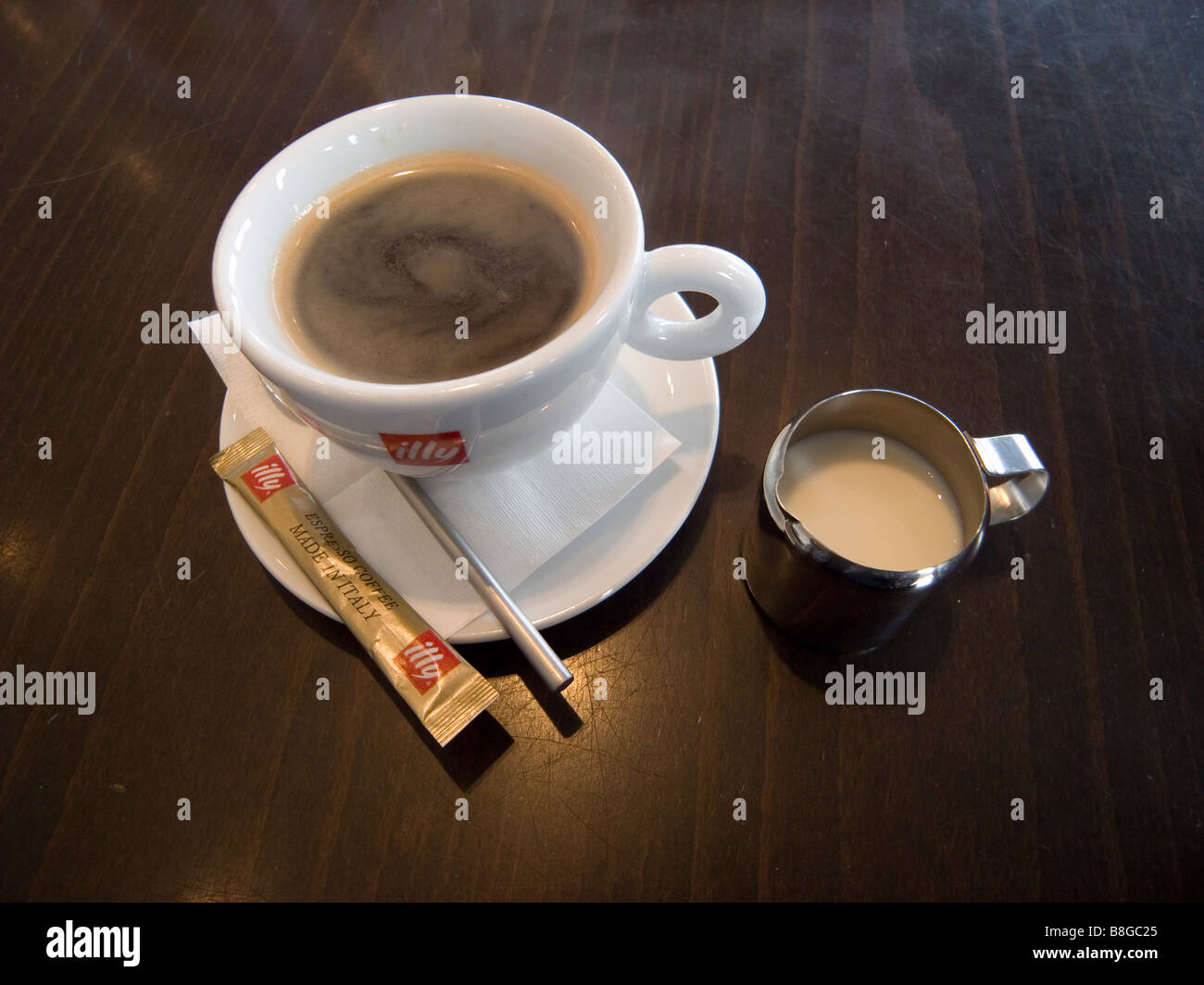 Regular Americano with cold milk cup of Illy coffee - Stock Image