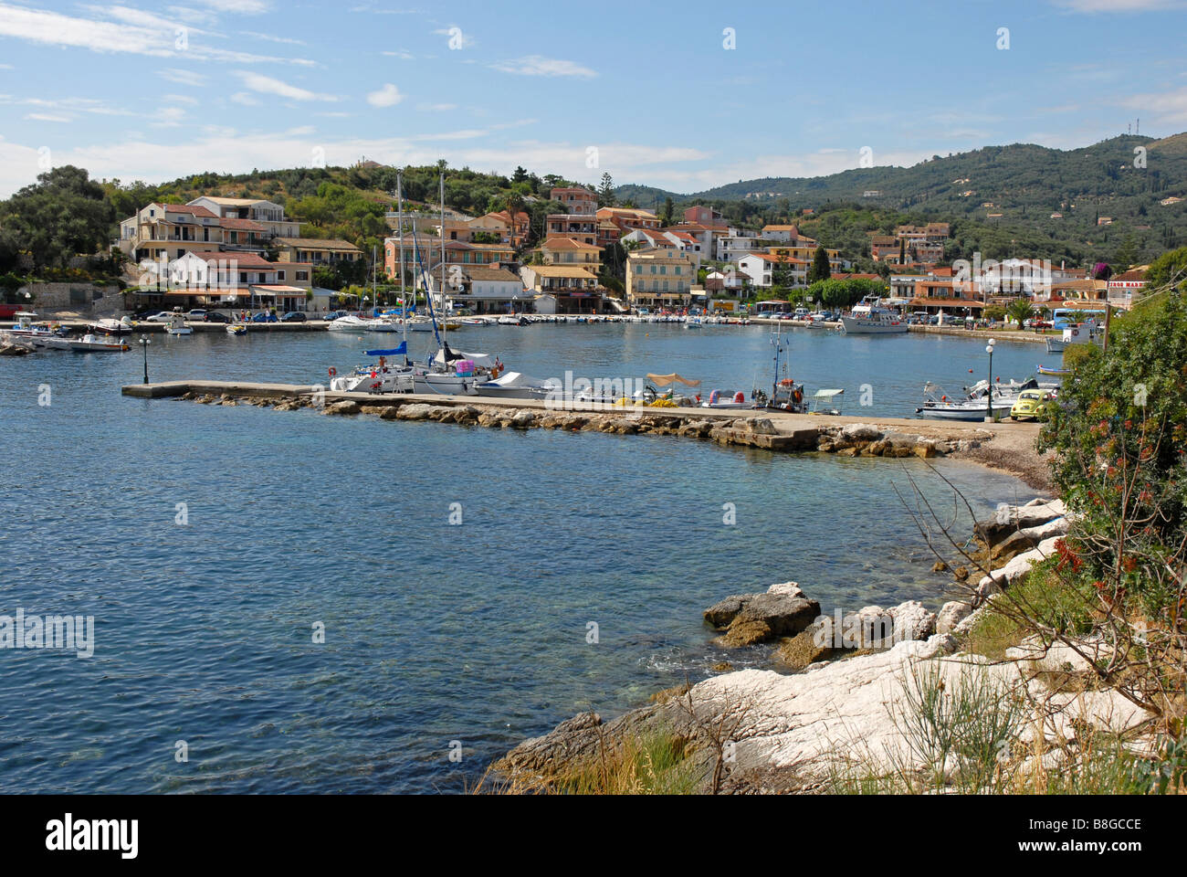 Kassiopi harbour, Corfu, with various boats tied to jetty and to harbour wall Stock Photo