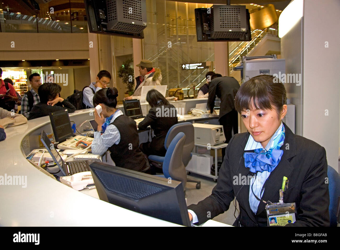 Ticket agent for All Nippon Airways at the Narita International Airport Tokyo Japan - Stock Image
