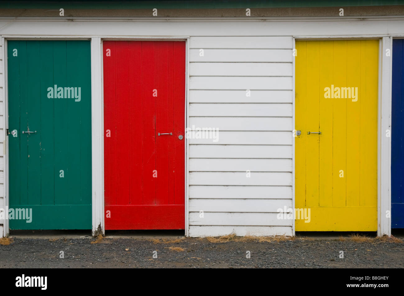 Brightly painted red yellow and green wooden doors - Stock Image