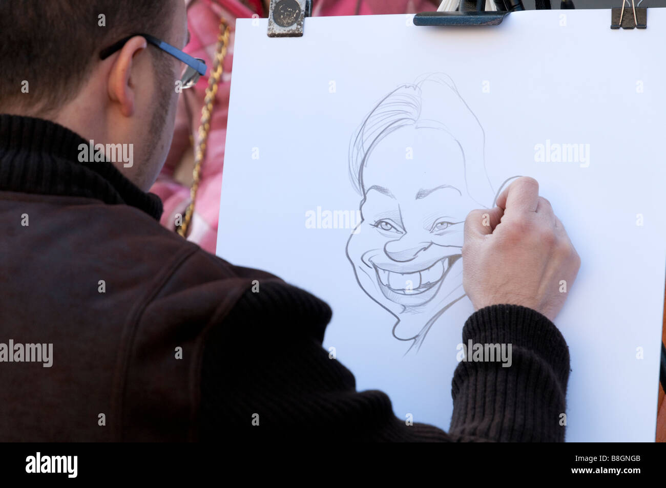 Street artist drawing a caricature of a young woman on La Rambla Barcelona Catalonia Spain - Stock Image