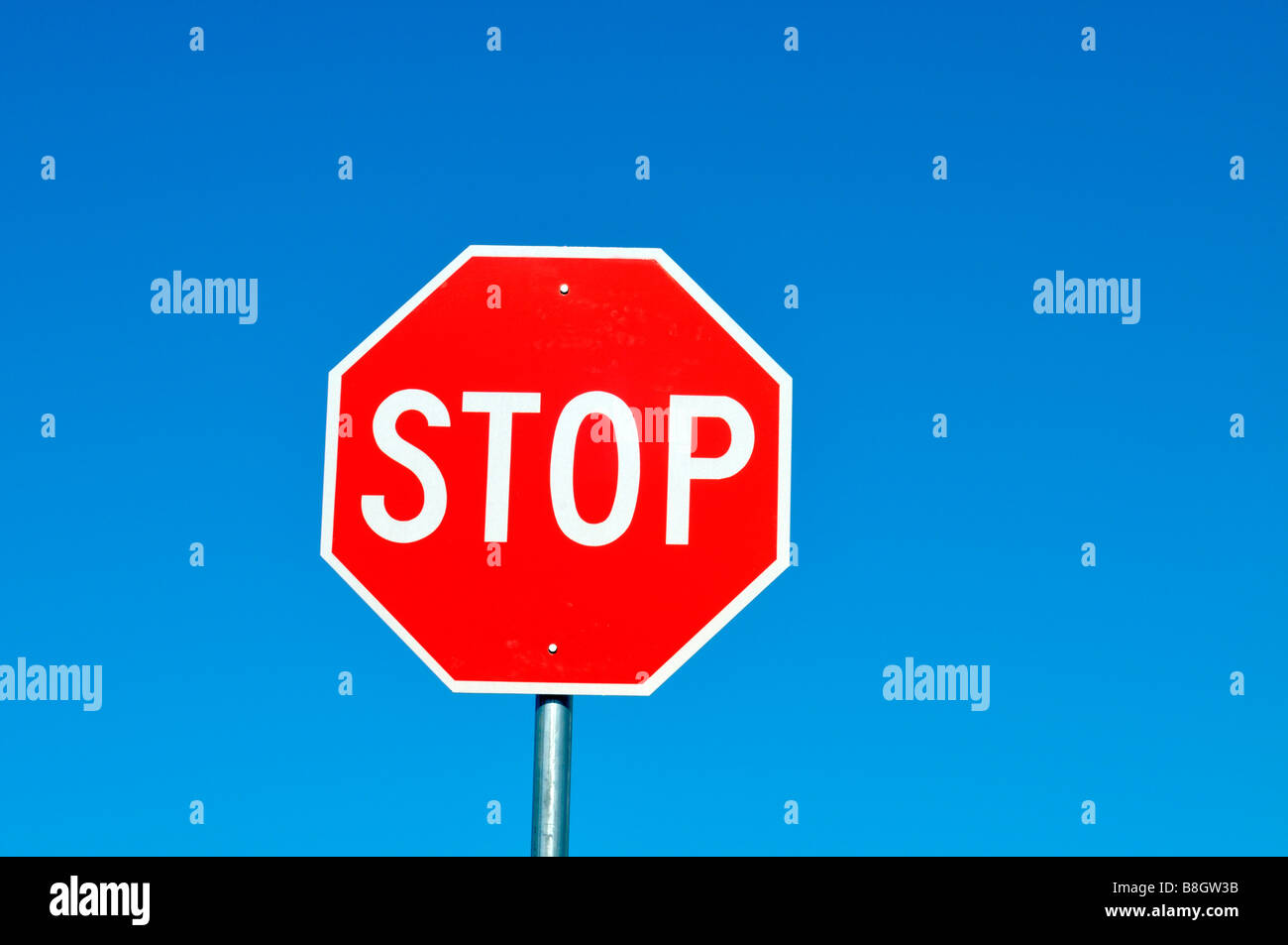 Red and white stop sign against solid clear blue sky - Stock Image