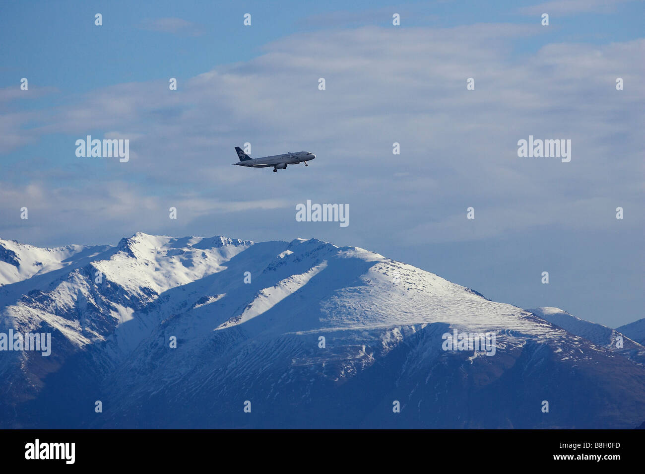 Air New Zealand Jet over Snowy Mountains near Queenstown South Island New Zealand Stock Photo