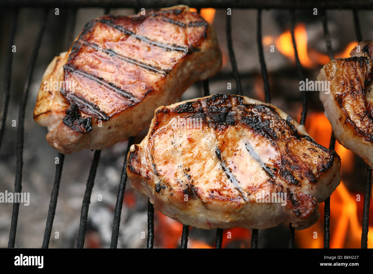Bangalow Pork chops grilling over an open fire - Stock Image