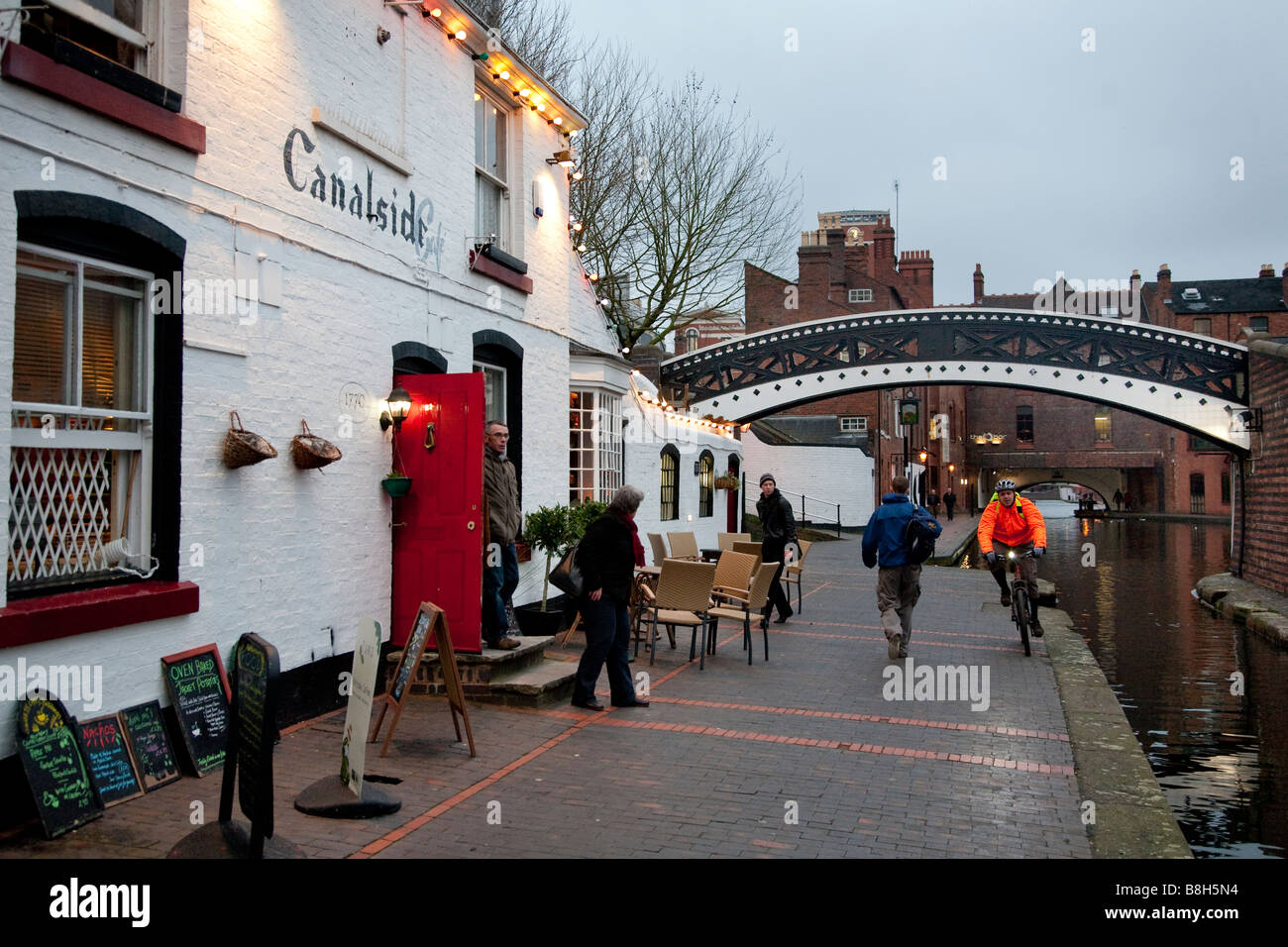 Canalside cafe, the Worcester Bar bridge and a busy towpath at dusk at the Gas Street Basin Birmingham - Stock Image