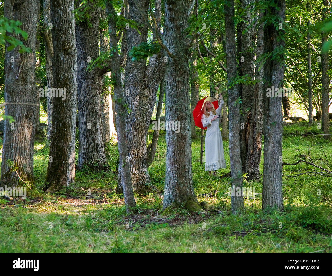 woman with red umbrella in forest Stock Photo