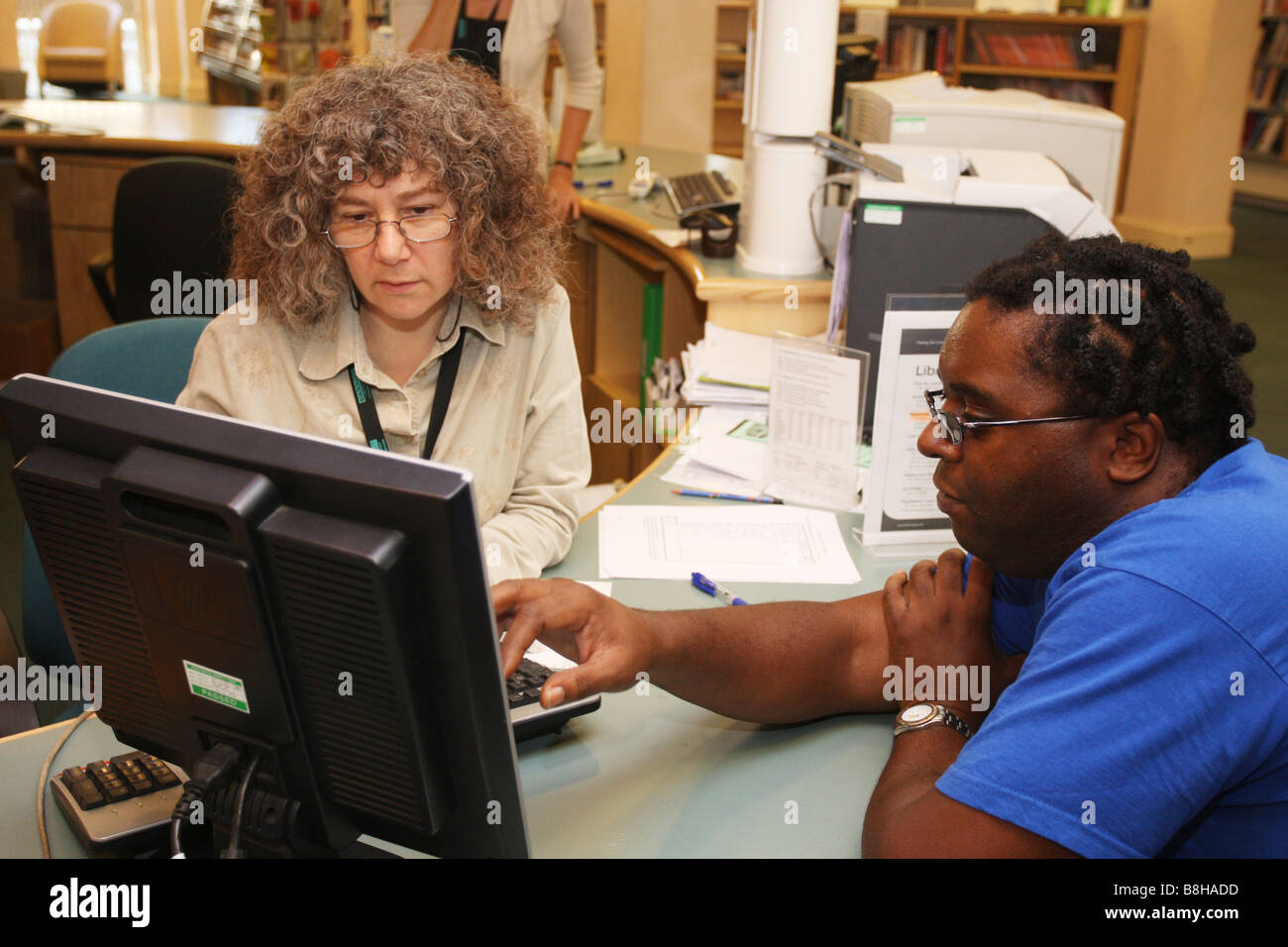 Man making enquiry at library front desk - Stock Image