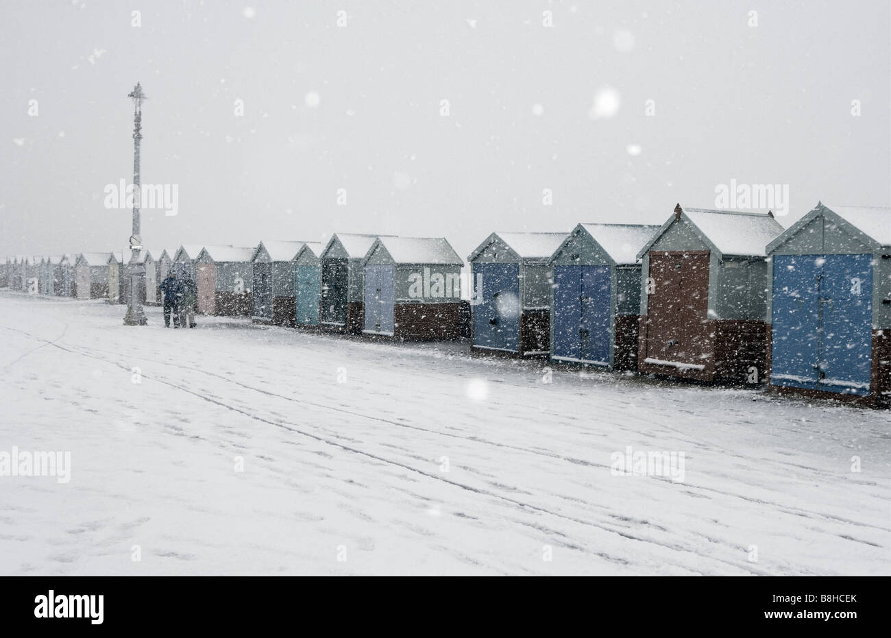 Snow falling on beach huts in Hove, England. - Stock Image