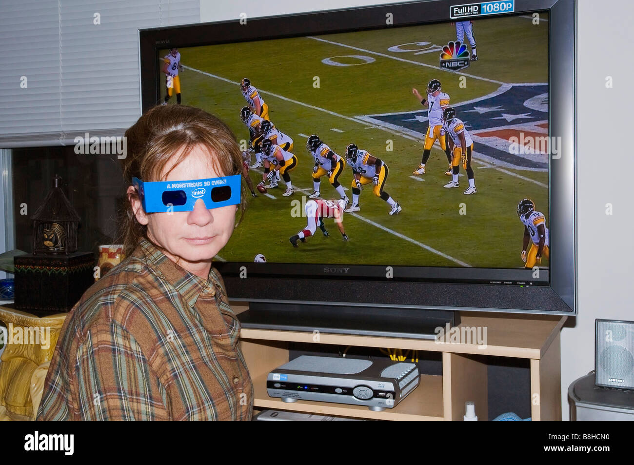 Woman wearing 3D glasses in front of TV with 3D Superbowl playing on television - Stock Image