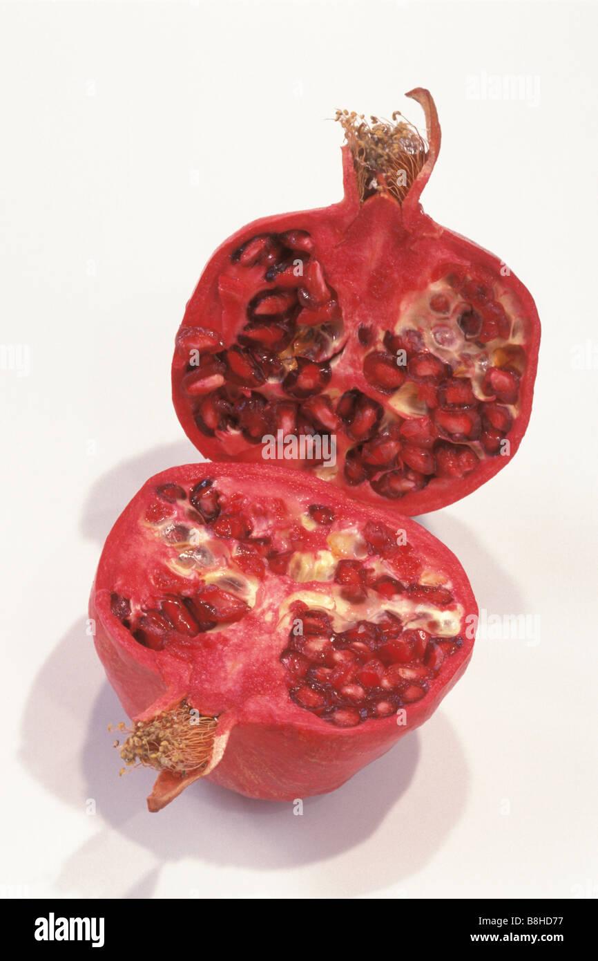 Pomegranate (Punica granatum), halved fruit, studio picture - Stock Image