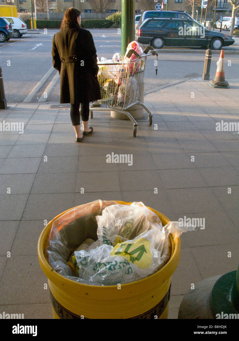 UK Woman waiting for taxi with shopping at a supermarket, with trolley full of plastic bags.London Photo by Julio - Stock Image
