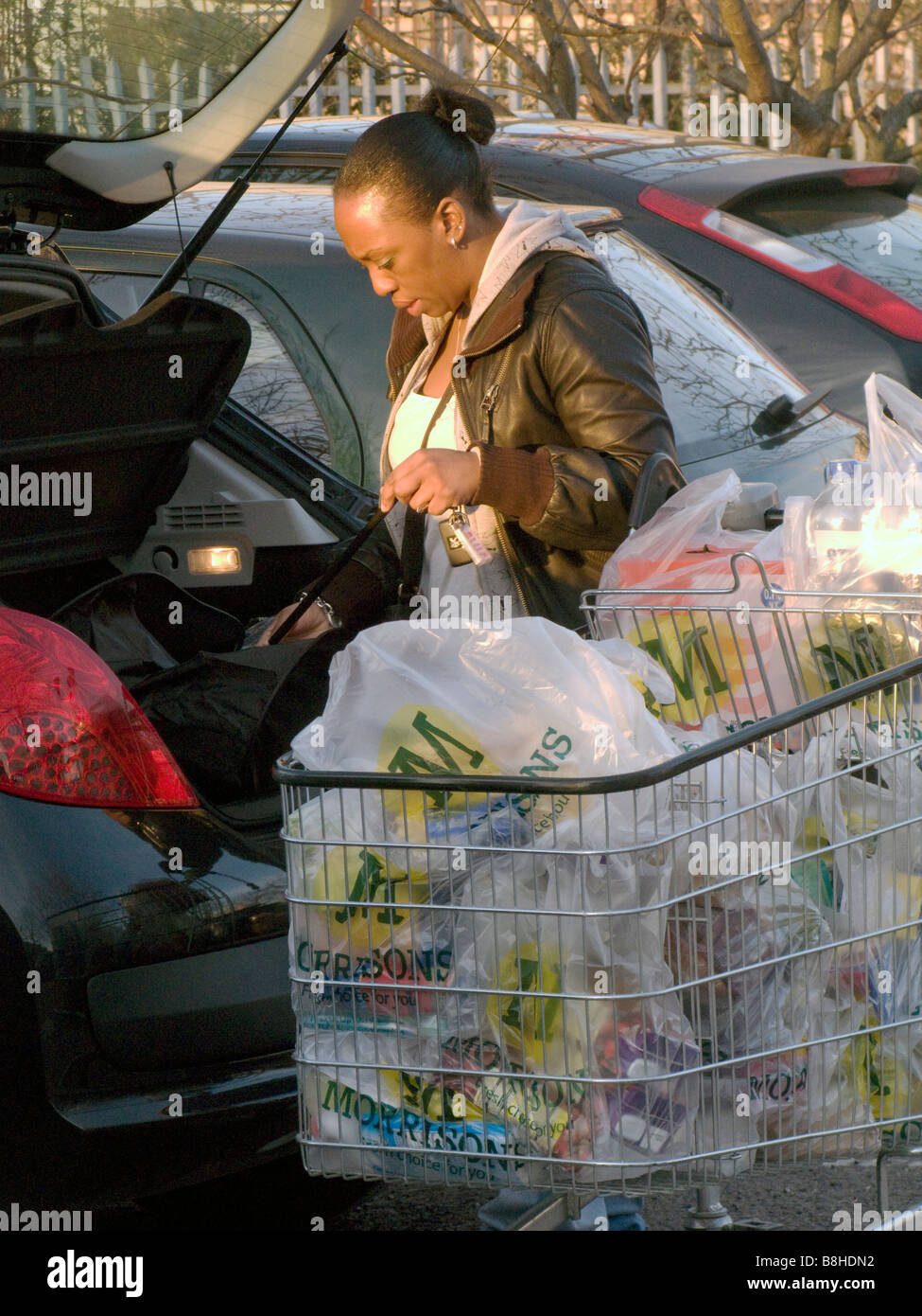 UK Woman loading a car with shopping at a supermarket, with trolley full of plastic bags.London Photo by Julio Etchart - Stock Image