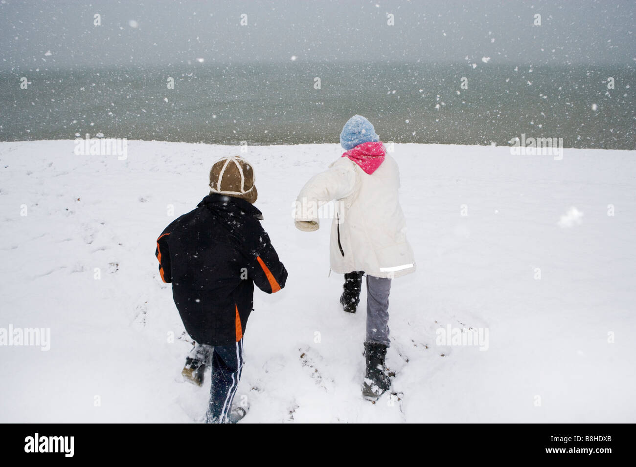 Children running on a snowy beach - Stock Image