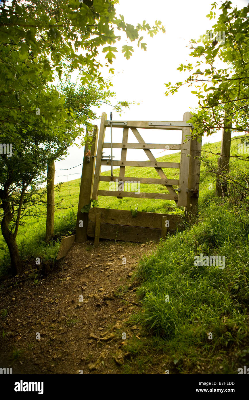 Wooden gate in the British countryside leading to open fields. - Stock Image