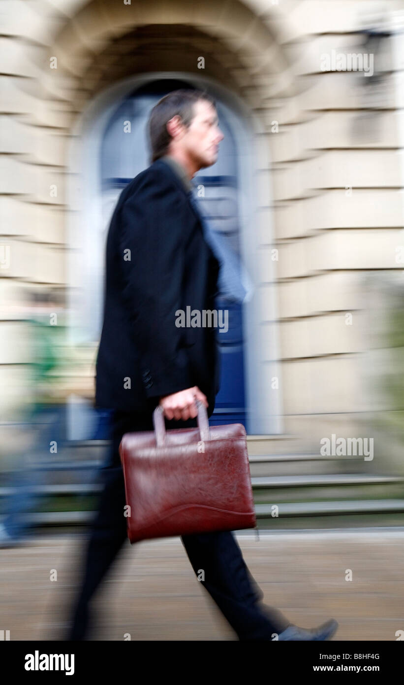 Businessman carrying a briefcase in financial district - Stock Image
