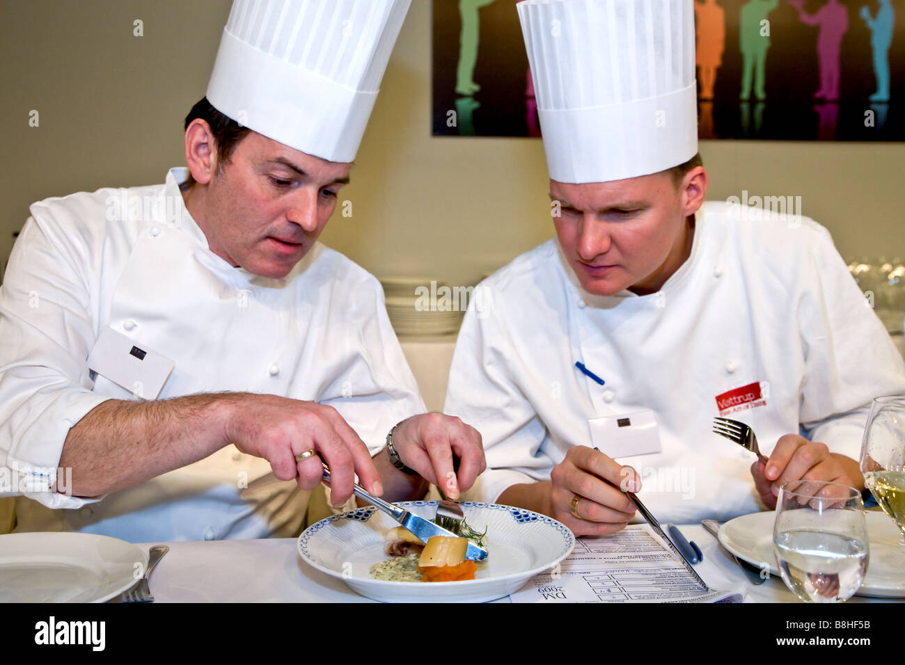 Two referees tasting the food at the cooking championship - Stock Image
