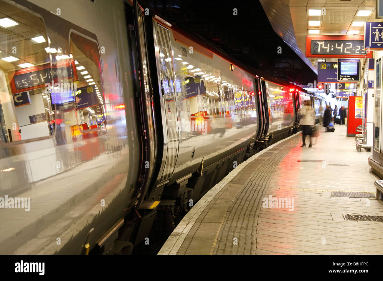 Train arriving at a platform at the train station - Stock Image