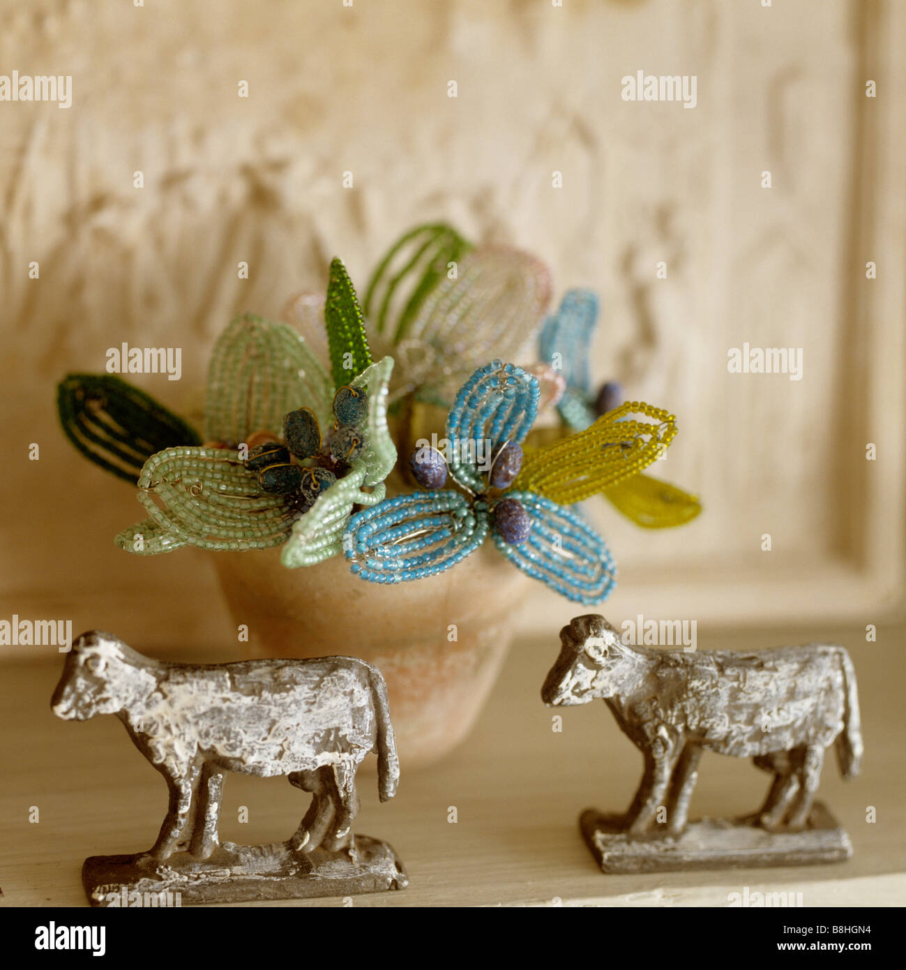 Detail of decorative French zinc cows in front of beaded flowers - Stock Image