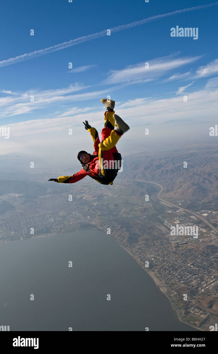 Skydiver is back flying in the blue sky over a big lake and having