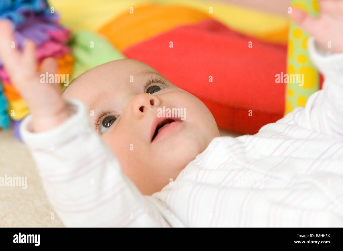 Happy baby playing lying on floor Stock Photo