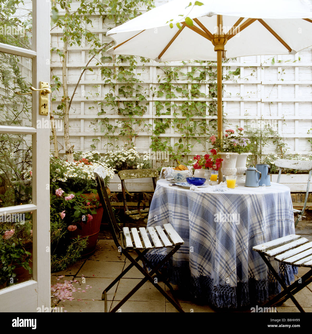 Breakfast table with blue and white checkered and fringed tablecloth and french iron cafe chairs in a London patio - Stock Image