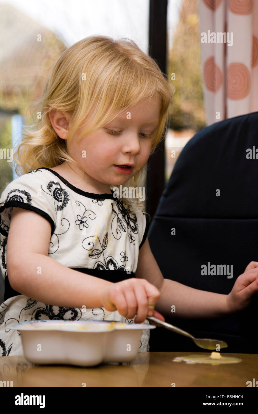 Young girl eats her dinner and make mess - Stock Image