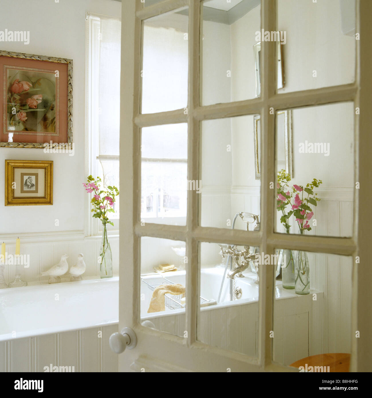 View through Georgian glazed door into a white bathroom - Stock Image
