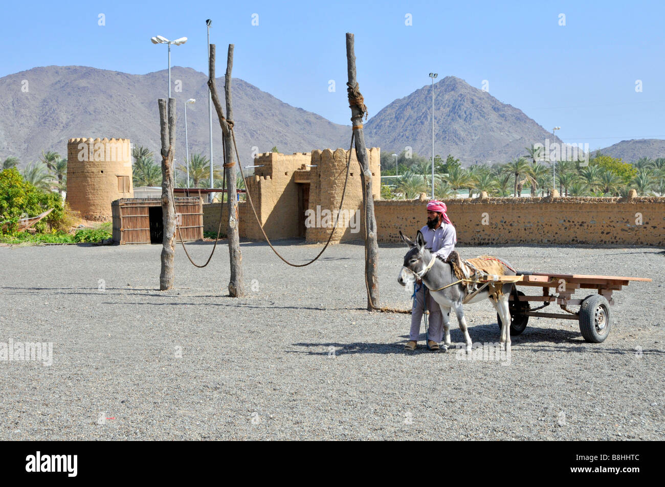 Fujairah Heritage Village walled compound with arab man beside donkey and cart - Stock Image