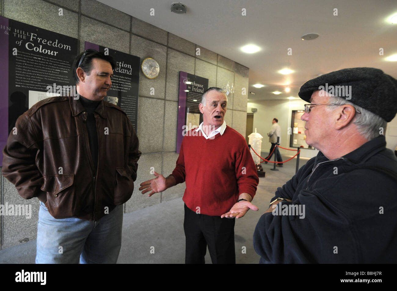 Waterford crystal occupier Ian Paul explains to tourists from that the factory is closed - Stock Image