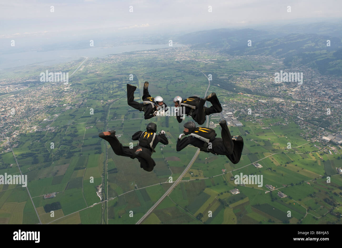 Skydiver team VIVA is flying a formation in the sky below clouds. 4-way RW skydive team is competing at the National - Stock Image