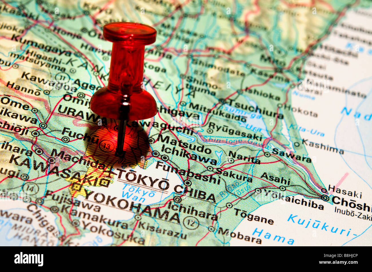Red pushpin on an atlas Tokyo Stock Photo
