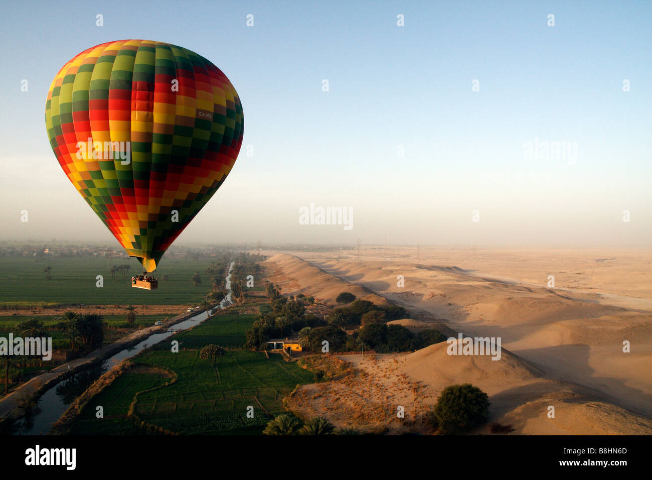 Hot air balloons flying over the desert villages and fields near Habu Temple near Luxor on the Nile in Egypt - Stock Image