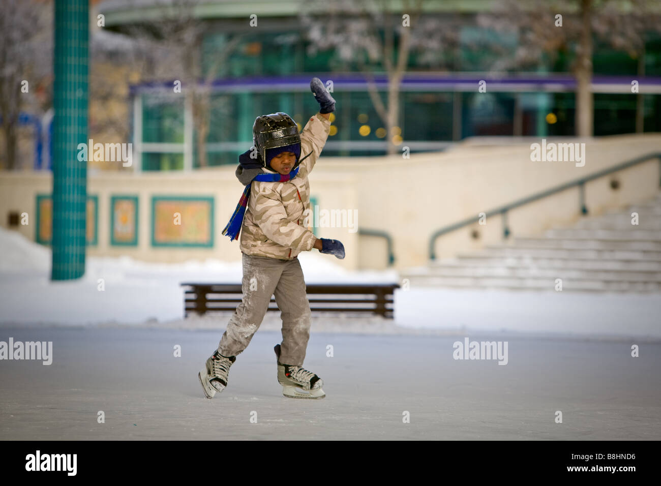 Young African American boy, learning to ice skate, outdoor rink. - Stock Image