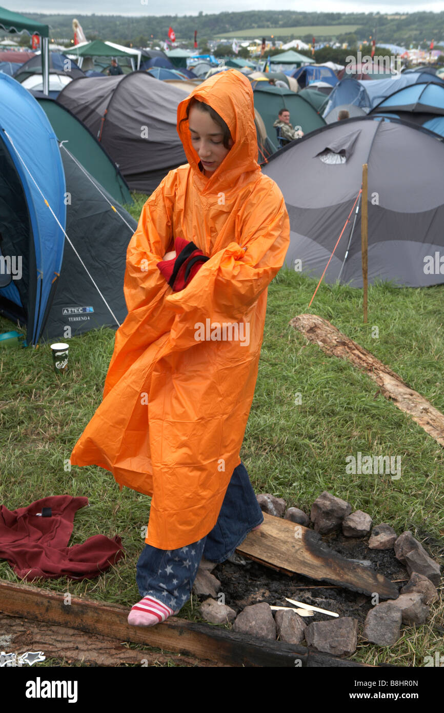 Glastonbury Festival 2007, teenage girl stands in campsite in bad weather wearing free Orange rain mac - Stock Image
