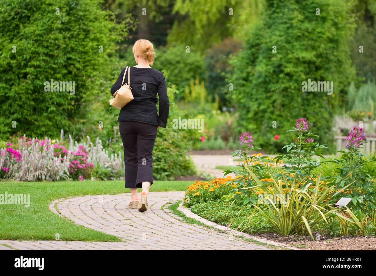 Woman walking down winding garden path, English Gardens, Assiniboine Park, Winnipeg, Manitoba, Canada. - Stock Image