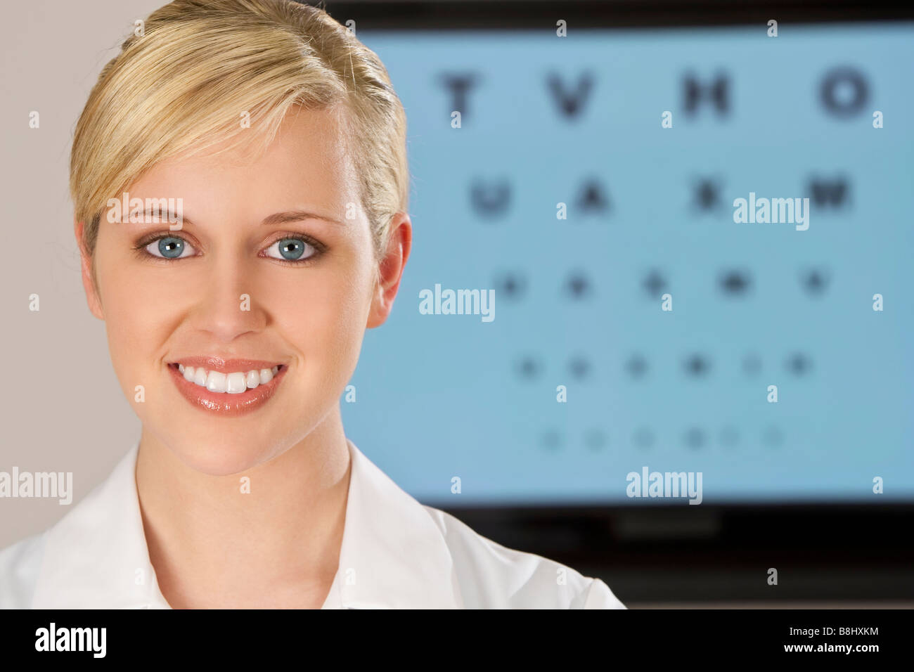 A beautiful female optician shot with an electronic eye test chart out of focus behind her - Stock Image