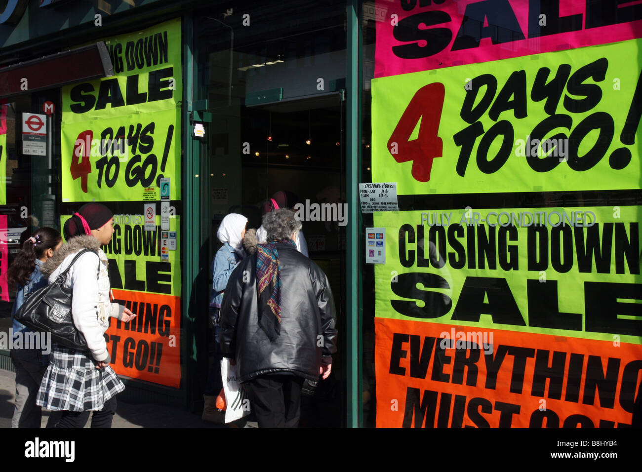 Shoppers rushing into a closing down sale shop, reflecting the difficult economic situation in the high street. - Stock Image