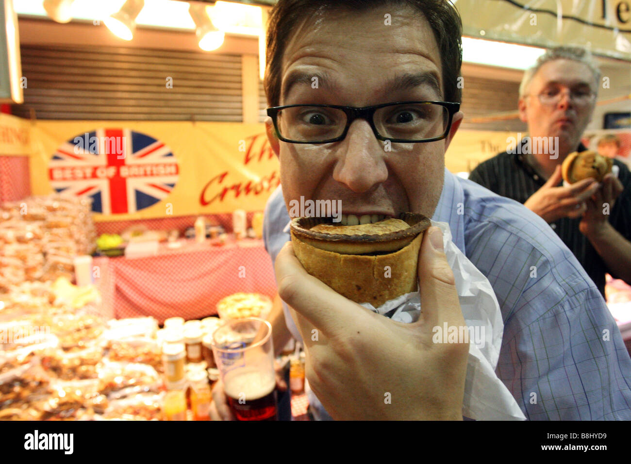 Biting in to pies at a British beer festival in Earls Court, London - Stock Image