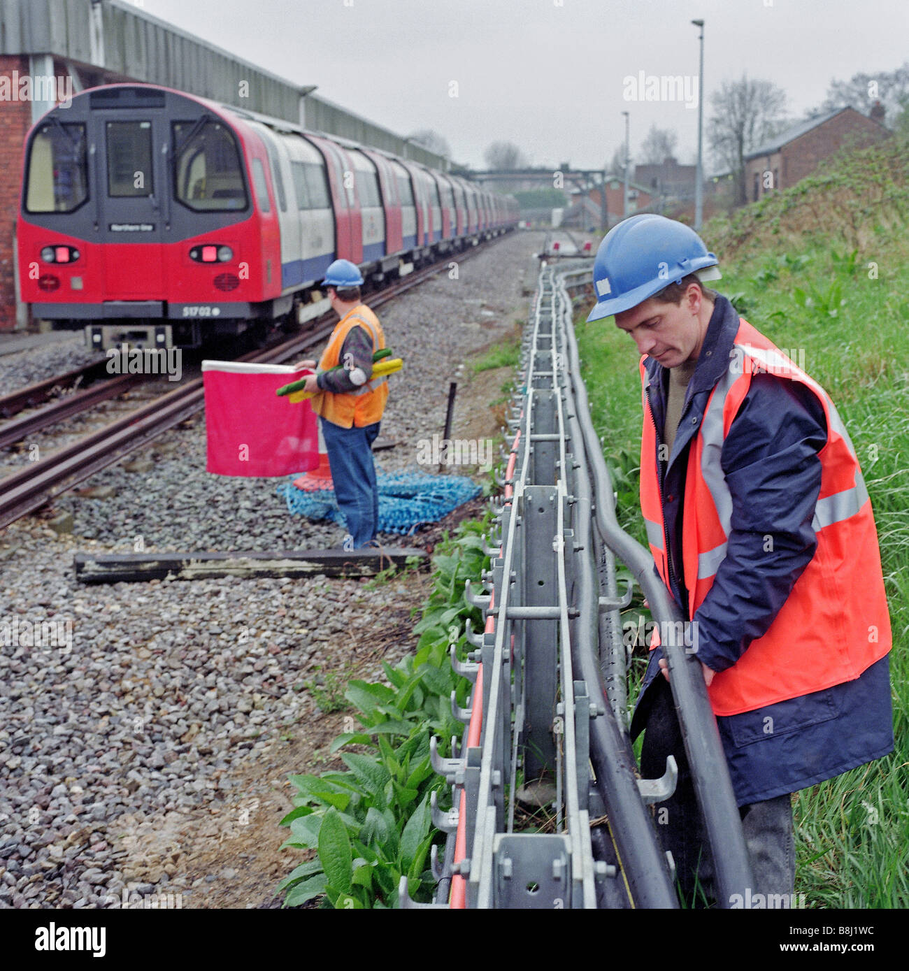 Engineer replacing power cable whilst a look-out holds a red