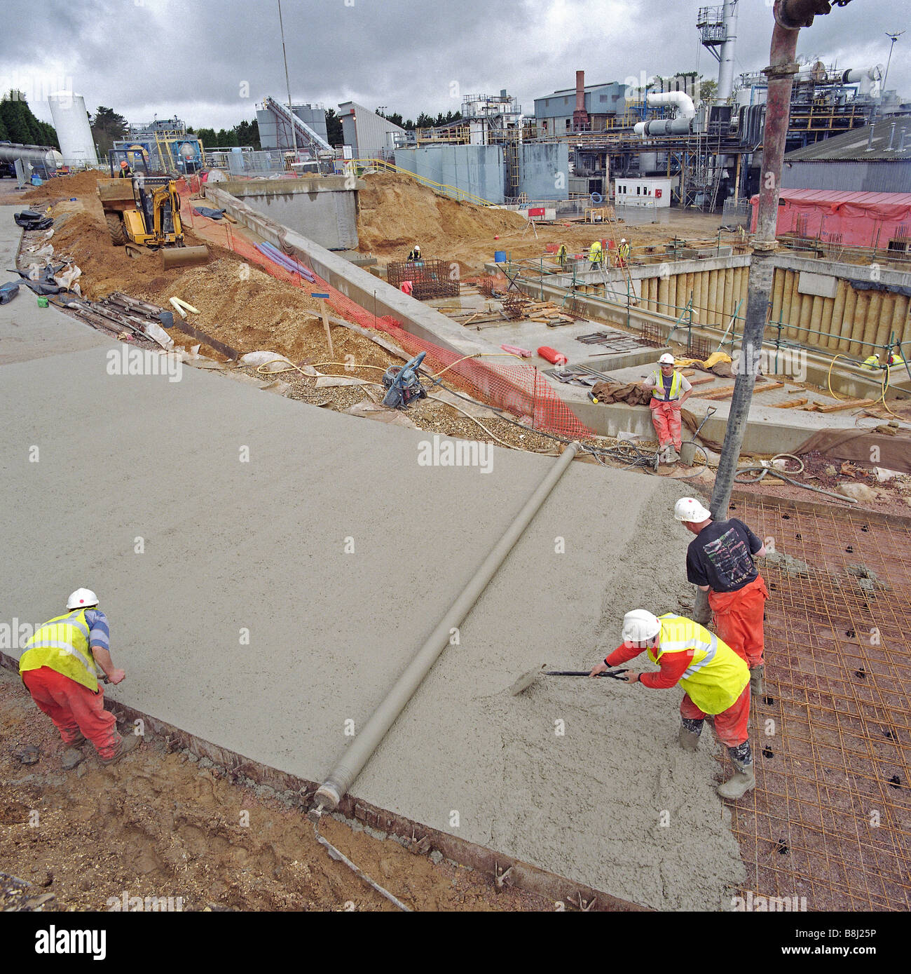 Contractors transferring liquid concrete by pump to build steel reinforced concrete access road at new Waste to - Stock Image