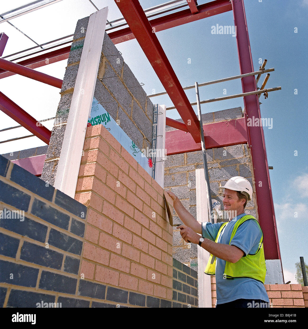 Skilled craftsman laying single skin of bricks in stretcher bond in a decorative pattern for exterior wall of a - Stock Image