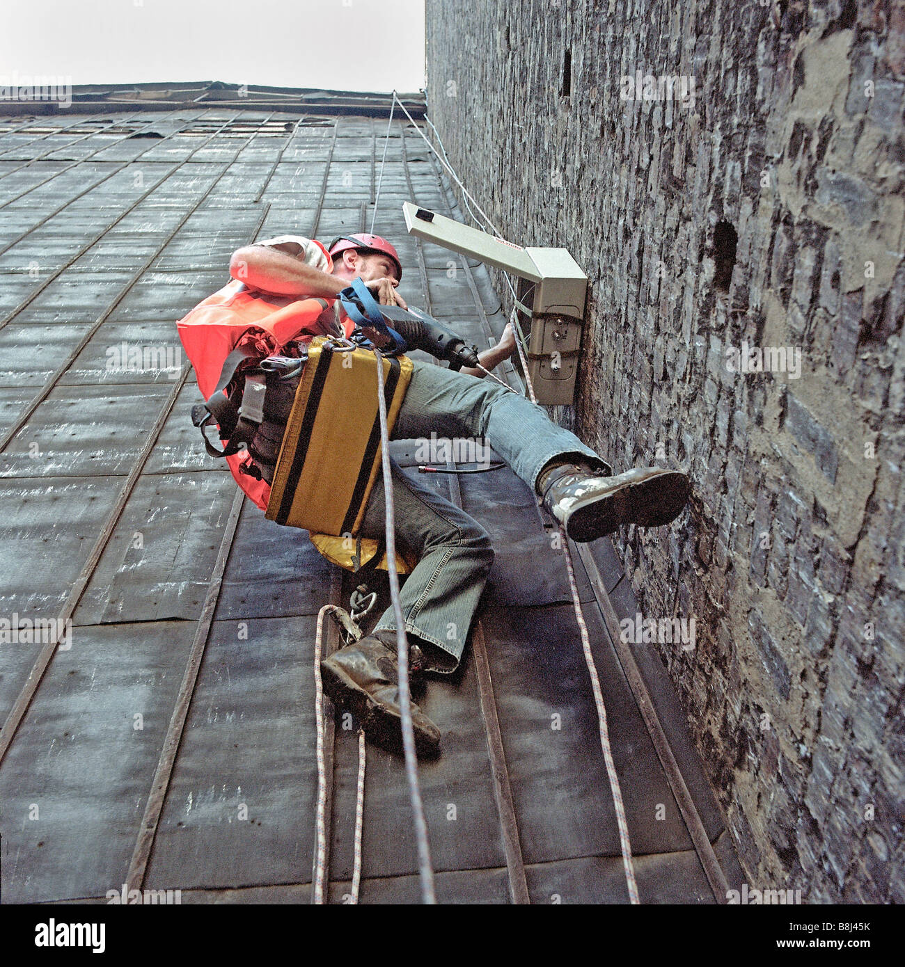 Contractor abseiling wall to install equipment to detect structural movement caused by construction on Channel Tunnel - Stock Image